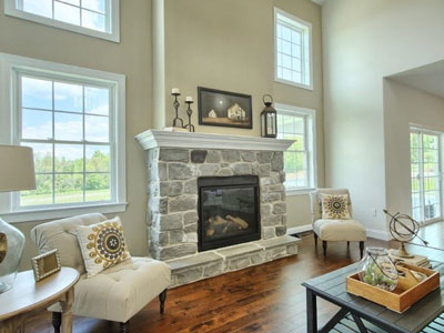 stone fireplace surrounded by windows and chairs